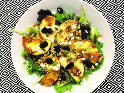 fresh salad featuring slices of pazazz apples all on a white plate on a mosaic black and white patterned table cloth.