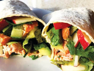 salmon, greens, and Pazazz apples slices encompassed in flour wraps on a white plate.
