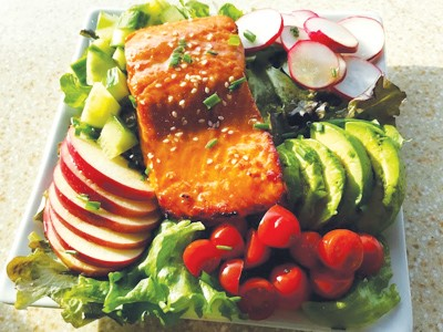 large piece of glazed salmon positioned atop a plate overflowing with fresh vegetables and slices of Pazazz apple. this all sites on a plane colored countertop