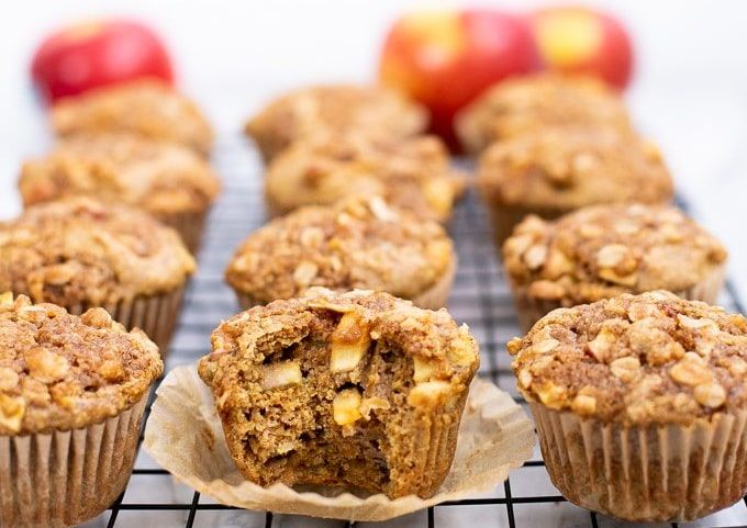 apple muffins sitting in four rows on a metal cooling rack. At the back of the photo three apples are blurred.