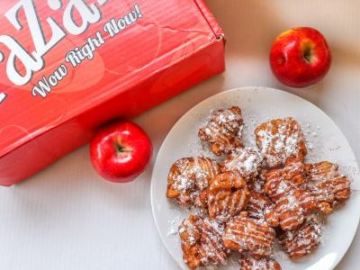 "Plate of apple fritters situated next to two shiny red Pazazz apples. A red Pazazz apple box that says ""Wow Right Now"" sits at the top left of the image."