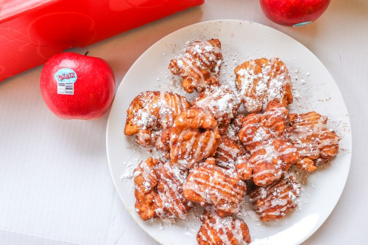 Pile of apple fritters situated on a white plate. They are drizzled with sugar glaze and a sprinkling of powdered sugar. A Pazazz apple sits to the left of the plate and to the upper right. A red apple box sits at the top of the image. All of this is set against a white background.