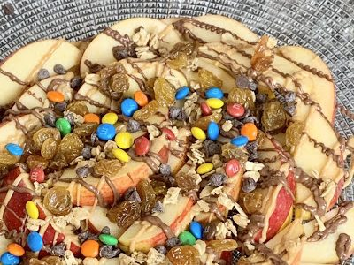 pile of apples covered in chocolate, peanut butter, m+ms, dried fruit, and chocolate chips.