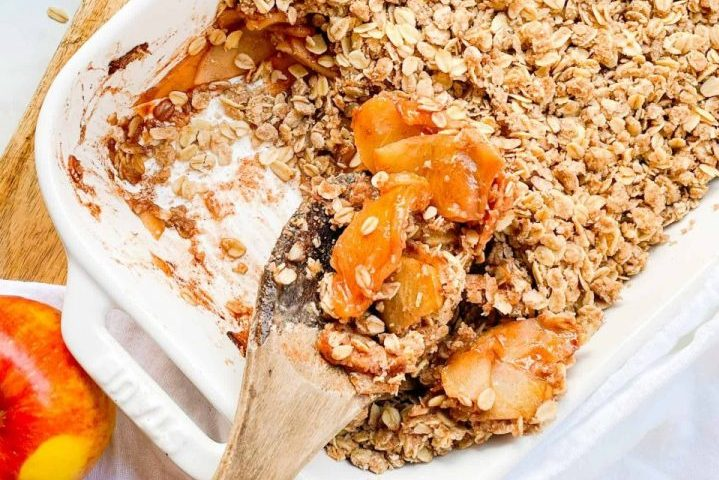 wooden spoon digging into white dish of Pazazz apple crisp with oat topping. All of this sits on a wooden countertop.
