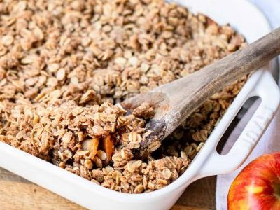 white baking dish filled with Pazazz apple crisp. A wooden spoon is digging into the right side of the crisp. A Pazazz apple sits to the right of the dish. All of this is positioned on a wooden countertop.